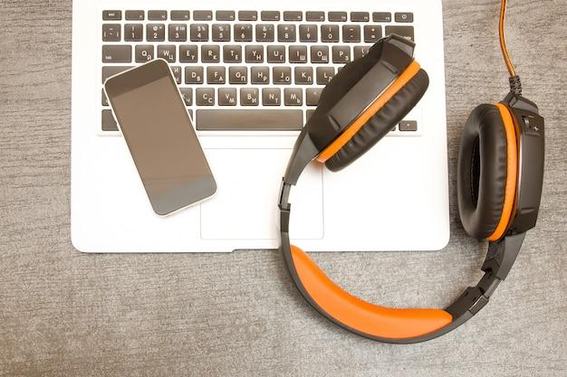 ノートパソコンのキーボード、ヘッドフォン、スマートフォン。職場。上面図