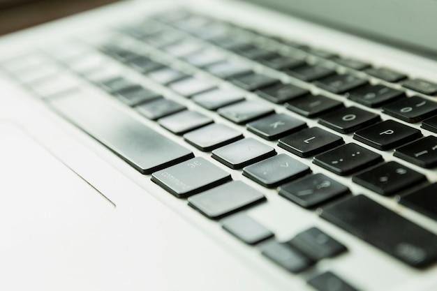 厳しい日差しの中でのラップトップキーボード。閉じる。
