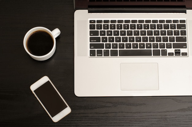 Laptop keyboard, phone and coffee mug on a black table, close-up