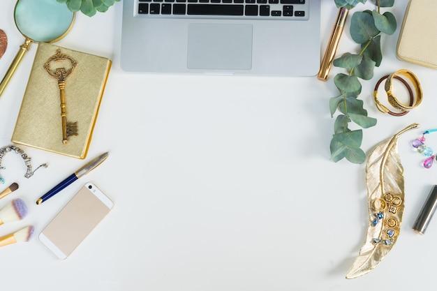 金色の女性のアクセサリーと緑の植物がフラットレイスタイルのシーンをモックアップするラップトップキーボード