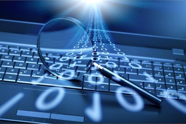 バイナリコードの図と虫眼鏡とラップトップキーボード