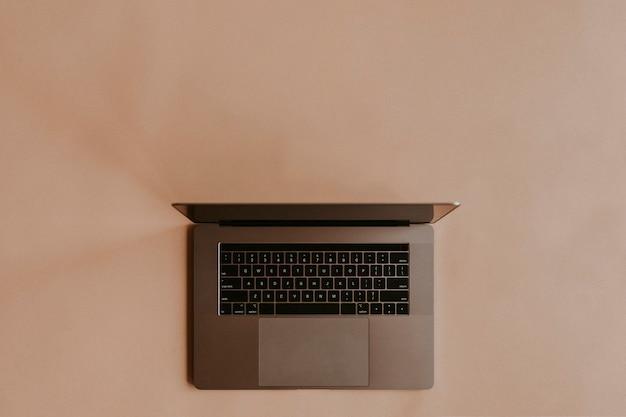 Ноутбук, лежащий на персиковом фоне