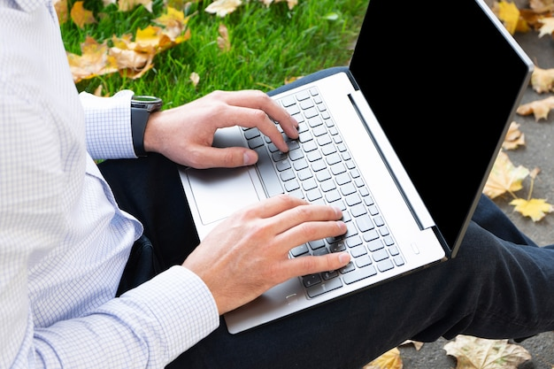 Laptop on man's lap in the park
