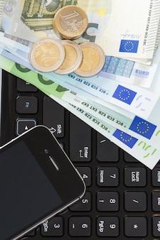 ノートパソコン、モバイル、現金をテーブルに