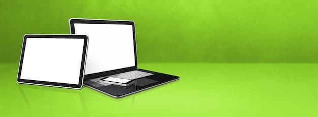 Ноутбук, мобильный телефон и цифровой планшетный пк на зеленом офисном столе.