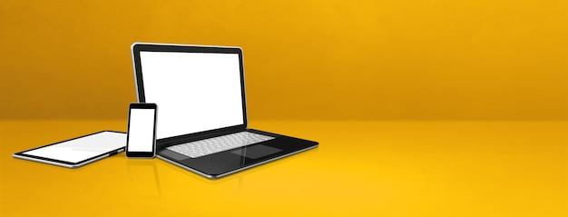 Ноутбук, мобильный телефон и цифровой планшетный пк на желтом офисном столе. фон баннера. 3d иллюстрации