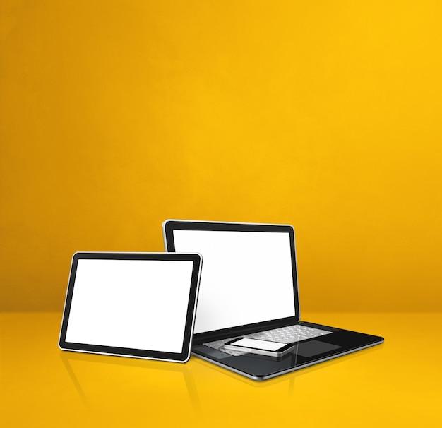Ноутбук, мобильный телефон и цифровой планшетный пк на желтом офисном столе