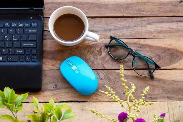 ノートパソコン、マウス、木製の背景にコーヒー1杯