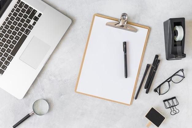 Ноутбук рядом с очками и канцелярскими принадлежностями