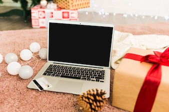 Laptop near plastic card, present boxes, fir snag and fairy lights