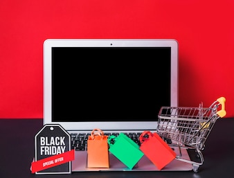 Laptop near toy packets, sign and shopping trolley