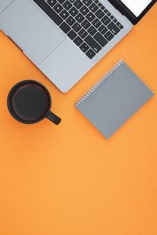 Ноутбук, тетрадь и чашка с кофе на оранжевой поверхности, вид сверху, на рабочем месте