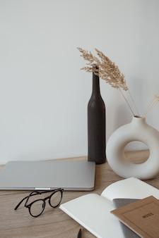 ノートパソコン、ノートブック、木製の背景にメガネ。ホームオフィスのワークスペース