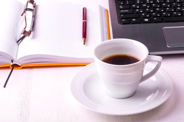 Ноутбук, блокнот с чашкой кофе и карандашом на деревянном столе