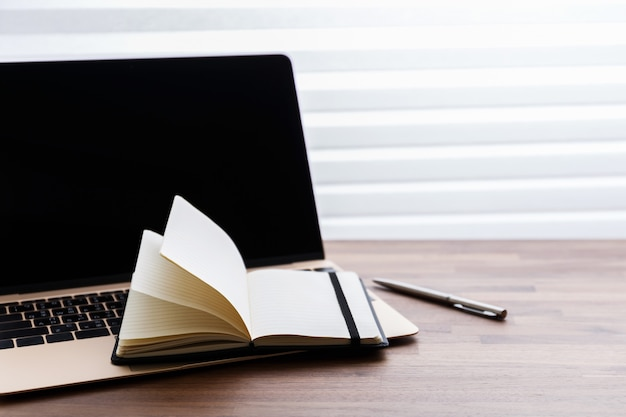Laptop and notebook on wooden table
