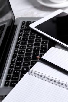 ノートパソコン、メモ帳、ペン、テーブルの上