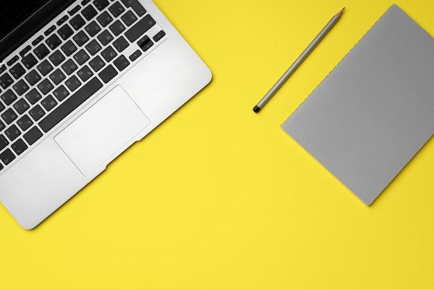 Ноутбук, блокнот и карандаш на желтом
