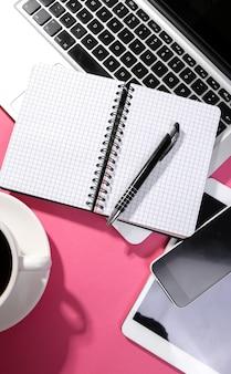テーブルの上のノートパソコン、メモ帳、スマートフォン、タブレット
