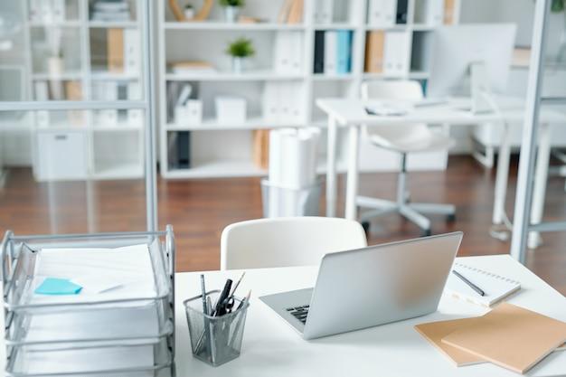 ラップトップ、メモ帳、いくつかの紙、鉛筆、メモ用紙、オフィスワーカーやクリエイティブデザイナーの職場