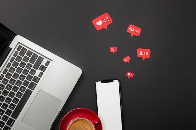 Ноутбук на черном рабочем столе с чашкой кофе, телефоном и знаком wi-fi, работа в социальных сетях. вид сверху. фото высокого качества