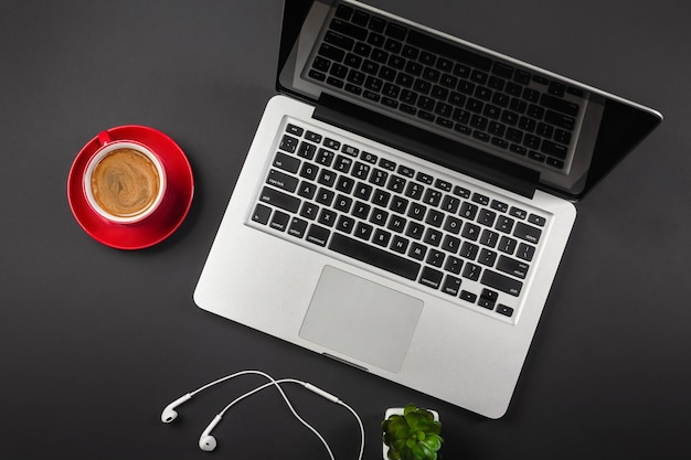 Ноутбук на черном рабочем столе с чашкой кофе, телефоном и знаком wifi работает в социальных сетях