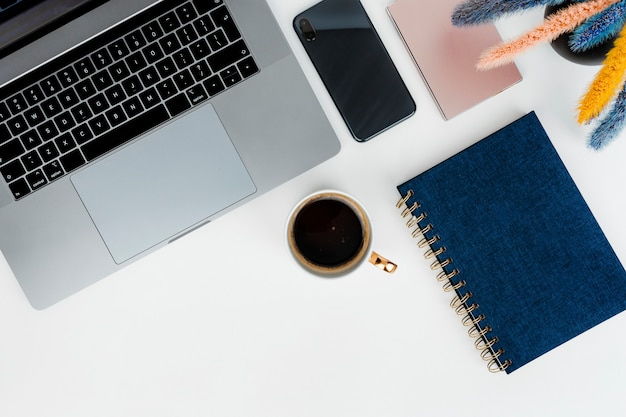 Ноутбук на столе с синим блокнотом