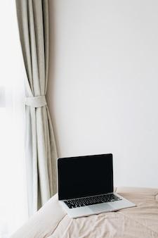 Ноутбук на кровати. минималистичная концепция дизайна интерьера. фрилансер бизнес дома концепция