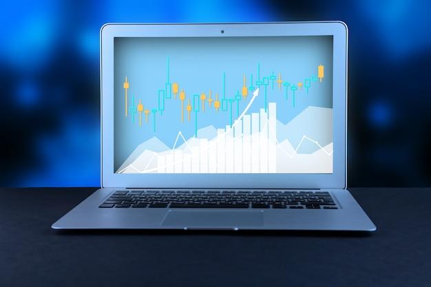 。オフィスのデスクトップ上のラップトップ、抽象的な背景を持つビジネスチャートと図、株式の金融と収入データのコンピューター分析、ビジネス経済学の概念。