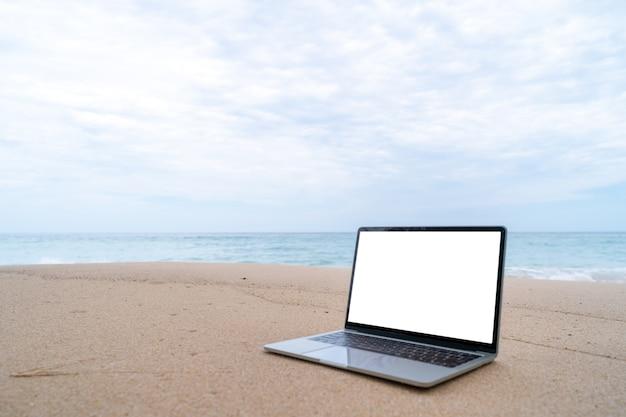 バックグラウンドで夏のビーチの砂の上のラップトップ。