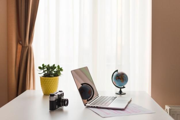 Ноутбук на столе рядом с камерой и земным шаром