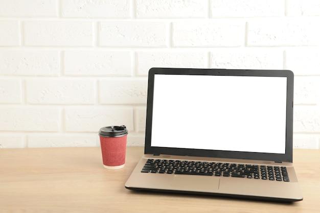 空白の画面とテーブルの上のラップトップ