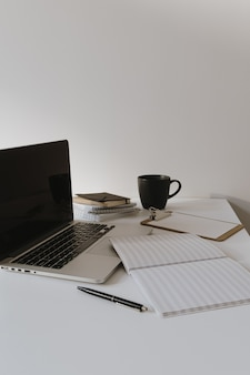 コーヒーカップ、白い壁に紙シートとテーブルの上のラップトップ