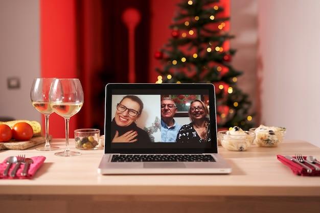 Ноутбук на рождественском столе. видеозвонок с семьей во время коронавируса.