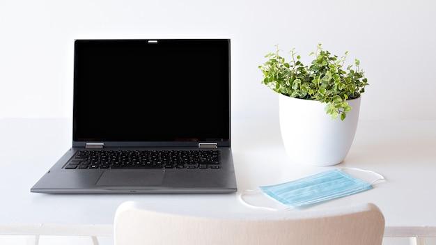 Ноутбук на белом фоне и концепция безопасности маски