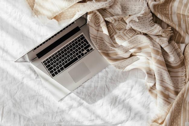 ベージュの格子縞の白いベッドの上のラップトップ。自宅で働くというコンセプト。朝の光。ライフスタイルの概念
