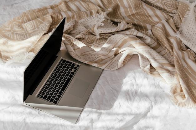ベージュの格子縞の白いベッドの上のラップトップ。自宅で働くというコンセプト。朝の光