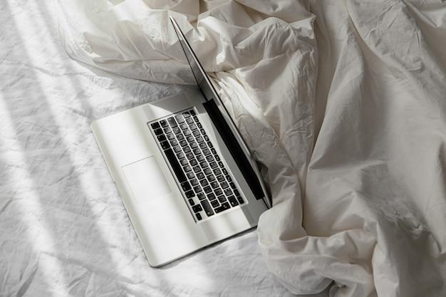 毛布と白いベッドの上のラップトップ。在宅勤務のコンセプト。朝の光