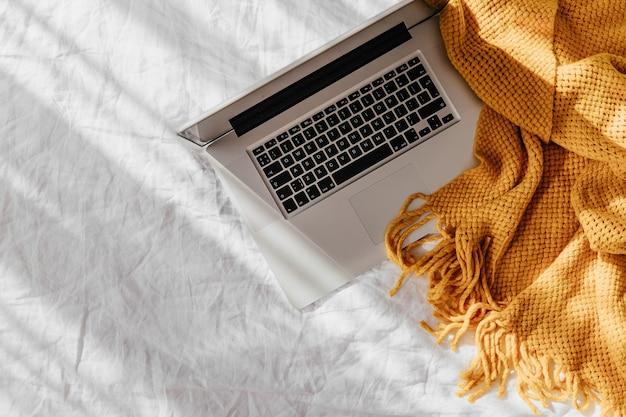 ニットの格子縞と白いベッドの上のラップトップ。自宅で働くというコンセプト。朝の光