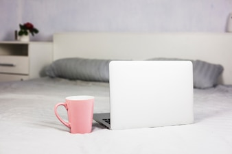 Laptop on white bed with coffee cup