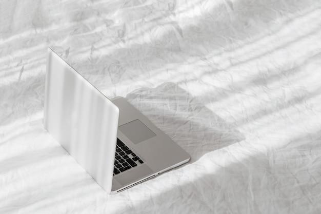 白いベッドの上のラップトップは家の概念で働きます。朝の光。ライフスタイルの概念