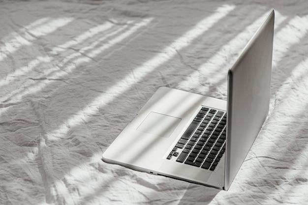 白いベッドの上のラップトップは家の概念で働きます。朝の光