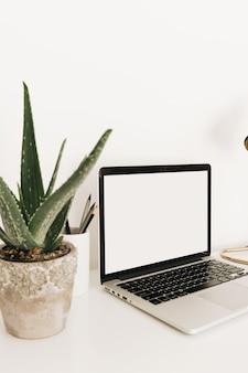 Ноутбук на белом столе с алоэ. минимальное рабочее пространство домашнего офиса с шаблоном макета