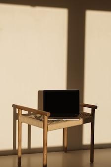 벽에 햇빛 그림자에 고리 버들 세공 벤치에 노트북
