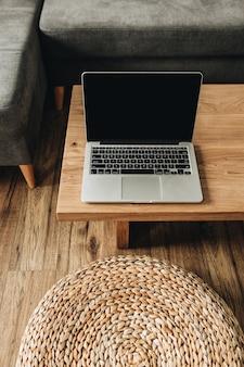 木製のテーブルの上のラップトップ。モダンなミニマルスカンジナビアの北欧のインテリアデザインのコンセプト。