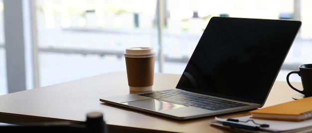 Ноутбук на рабочем месте с бумажным стаканчиком кофе