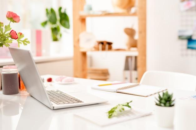 Ноутбук, открытый блокнот с ручкой и другими канцелярскими принадлежностями на рабочем месте современного креативного дизайнера