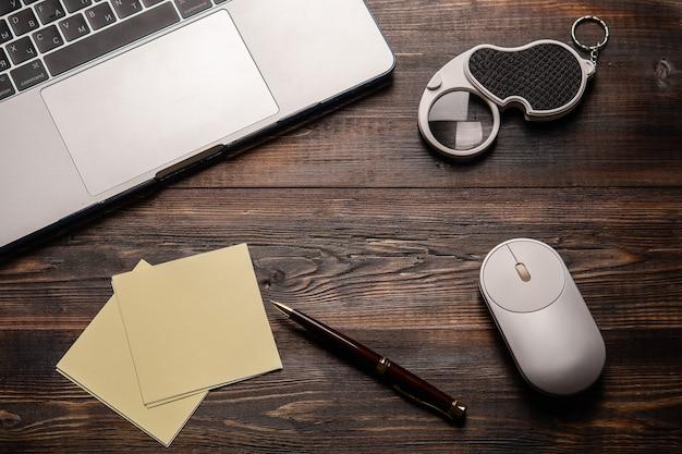Ноутбук открыл лупу, ручку для мыши и бумагу для заметок на темном деревянном столе крупным планом