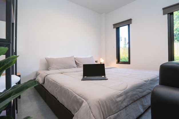モダンなベッドルームのベッドの上のラップトップ Premium写真