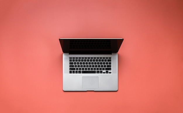 Laptop on pale red background overhead view