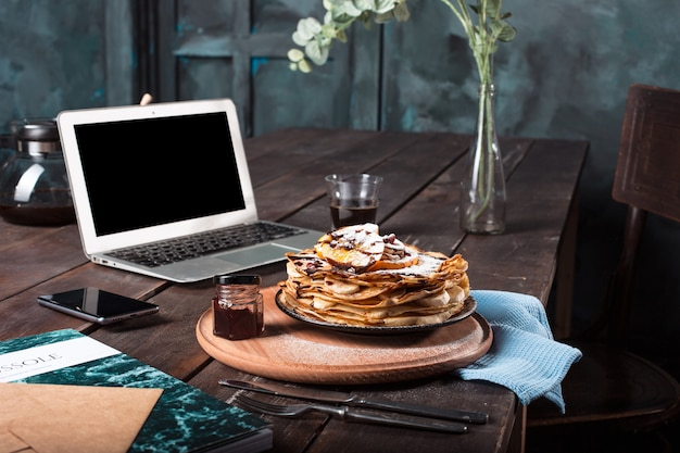 Laptop and pancakes with juice. healthy breakfast